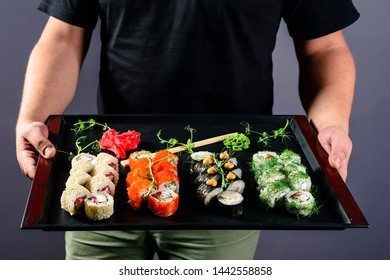 Gallant Waiter in a black apron holds dishes with sushi set in the shape. waiter with a set of rolls of sushi on a tray