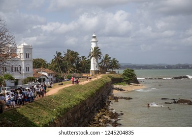 Galle Fort, Sri Lanka - July 27, 2018: The lighthouse and people walking on the fort wall