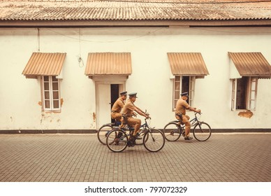 GALLE, SRI LANKA - DEC 23, 2017: Group of policemen in retro uniform riding bicycles in historical city on December 23, 2017. Galle Fort is the UNESCO World Heritage Site, built first in 1588