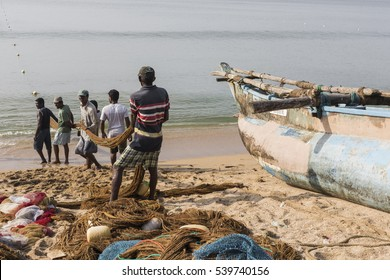 GALLE, SRI LANKA - DECEMBER 09, 2016 : Fishermen stood and work in the a boat on the beach at Galle city.
