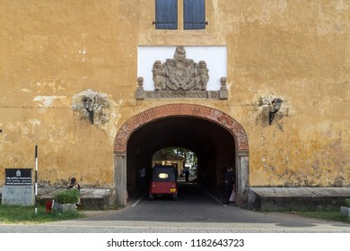 Galle, Sri Lanka - July 28, 2018: A tuk tuk driving through the old gate of the historic fort