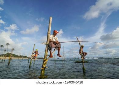 Galle, Sri Lanka - October; Stilt fishermen fishing in traditional way near Galle in Sri Lanka.