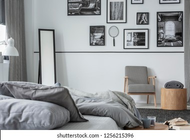 Gallery of black and white photos on wall of stylish bedroom interior with mirror, retro armchair and wooden table with blanket