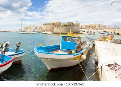 Gallipoli, Apulia, Italy - Fishing boat at the seaport in front of the town wall