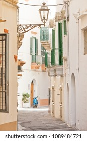 Gallipoli, Apulia, Italy - A traditional street lamp in a historical lane with a motor scooter