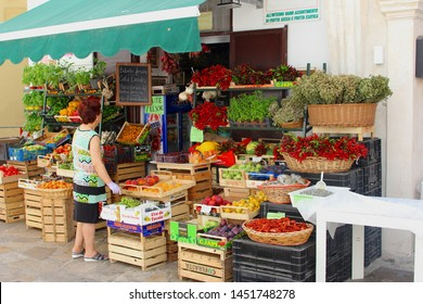 GALLIPOLI, PUGLIA, ITALY - July 8, 2019. Italian woman with gloves buys fruits and vegetables in small grocery store, mini market with outdoor display of regional food products in neighborhood street.