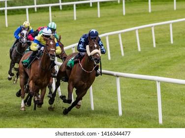galloping race horses and jockeys