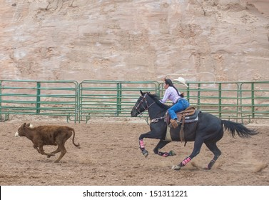 GALLUP , NEW MEXICO - AUGUST 10 : Cowgirl Participates in in a Calf roping Competition at the 92nd annual Indian Rodeo in Gallup, NM on August 10 2013