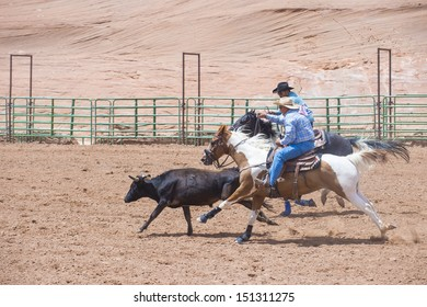 GALLUP , NEW MEXICO - AUGUST 10 : Cowboys Participates in a Steer wrestling Competition at the 92nd annual Indian Rodeo in Gallup, NM on August 10 2013