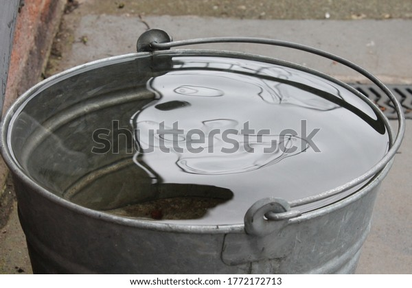 Galvanised metal bucket full of rain water with wind ripple and reflection on the surface