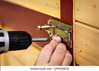 Galvanized door lock bolt or door bolt is screwed to a wooden door with a cordless screwdriver