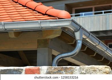 Galvanisierter Regenschaden, Regenwasserrohre und Anschlussschnecke auf Fliesenboden
