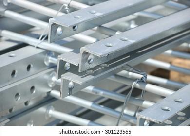 Galvanized steel tower ladder bundle in industrial stockyard.