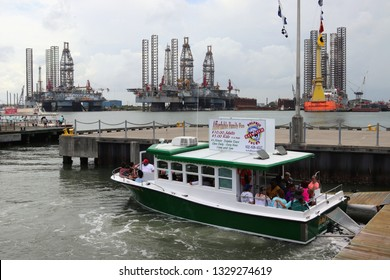 GALVESTON, TEXAS, USA - JUNE 9, 2018: Tourists on a Baywatch Dolphin Tour boat in the Port of Galveston. Galveston harbor is the natural habitat of dolphins. In the background oil rigs.