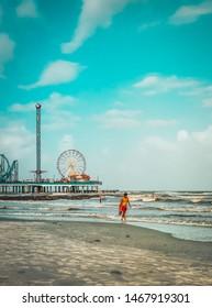 Galveston, TX, US - June 23, 2019: Lifeguard walks the shoreline warning swimmers of dangerous surf conditions  on Galveston Island Texas.