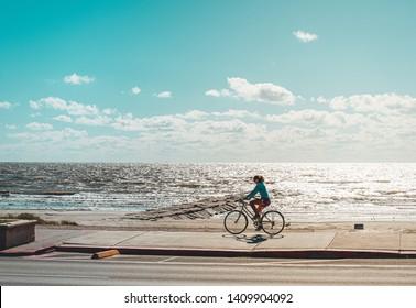 Galveston, TX, US - Nov 03, 2018: Woman riding her bicycle on Seawall Blvd. in Galveston Texas.