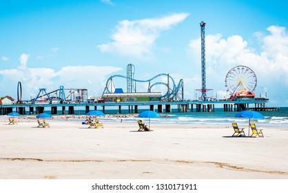 Galveston, TX, US - October 04, 2018: View of  beach umbrellas and Pleasure Pier  amusement park on Galveston Island Texas.