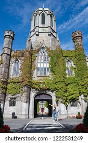 Galway City, Ireland - 29th July 2018: Tourists walking by the archway entrance of the Quadrangle building in Galway city University.