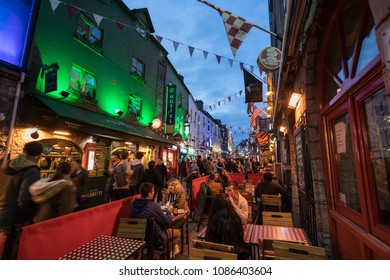 GALWAY CITY, IRELAND - 4th May, 2018:  People enjoying bars and Restaurants on Quay street in the popular Latin quarter area of Galway city at night.