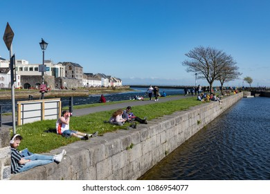 GALWAY CITY, IRELAND - 5th May, 2018: People enjoying a sunny spring day along the bank of Corrib river in the Claddagh area of Galway city, Ireland