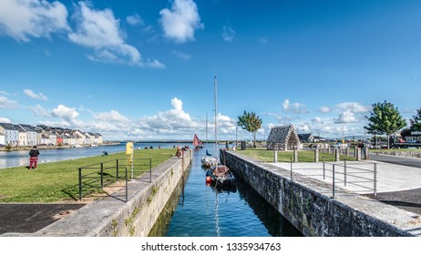 A Galway Hooker passes the Long Walk as it enters the Claddagh basin, Galway, on a sunny July day.