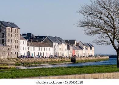 Galway, Ireland - 03.01.2021: People enjoy warm weather on River Corrib, Claddagh basin. Warm sunny day, Cloudy sky, Covid 19 lock down time