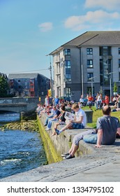 Galway, Ireland - 09.08.2012: The Claddagh Galway in Galway, Ireland. People sitting at shore enjoying sunny summer day.