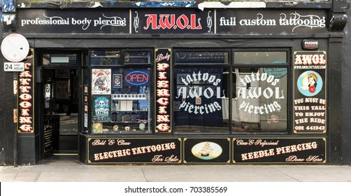 Galway, Ireland - August 3, 2017: Small business black facade of tattoo parlor plastered with slogans and advertisements. Open door and display windows.