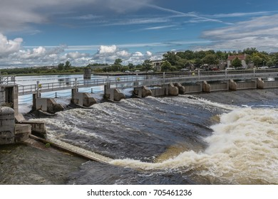 Galway, Ireland - August 5, 2017: Water control dam with open and closed floodgates. Fast flowing white water on Corrib River under blue and white cloudscape. Green trees in background.