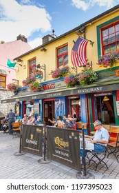 GALWAY, IRELAND - NOVEMBER 18, 2012: Men relaxing on a summer's day at The Quays bar in Shop Street in Galway,  Ireland.