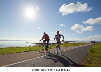 GALWAY, IRELAND - OCTOBER 6: Pauline Curley (3827), lead woman, escorted with race marshal, compete during annual Galway Bay Half Marathon and 10K, on October 6, 2012 in Galway, Ireland.