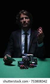 Gambler man in casino sitting at table with cards and poker chips