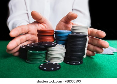 Gambler man hands pushing large stack of colored poker chips across gaming table for betting. Casino concept.