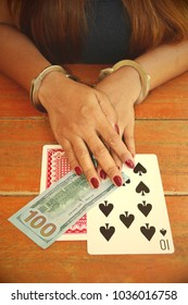 Gambling addict woman cuffed hands over playing cards and money on the table