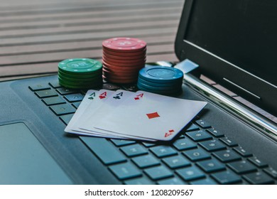 Gambling addiction concept.  Play poker online on internet. Cards and poker chips on a keyboard computer.
