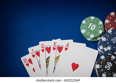 Gambling chips and poker card on blue felt background