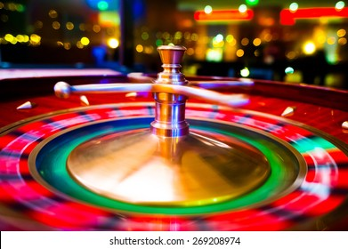 Gambling with colorful spinning fortune roulette wheel in casino with swallow depth of field on bokeh casino and city lights in the background