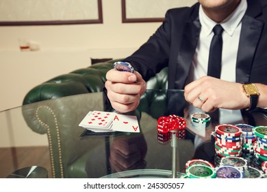 Gambling, male players. On the gaming tables are red dice, cards, casino chips - concept gambling addiction. People tend to take risks and to gambling. Play and win the success of the player.