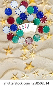 Gambling on Vacation Concept - White Sand with Yellow Stars, Colored Poker Chips and Four Ace Cards.