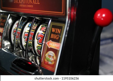 Gambling slot machine in close up view with sevens in a row
