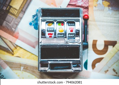 Gambling slot machine in close up view on money background.