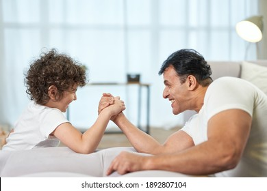 Game for boys. Cute latin boy and his father having fun together at home while armwrestling lying on the couch