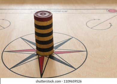 A game of carrom with arranged stones on the board around the center star.