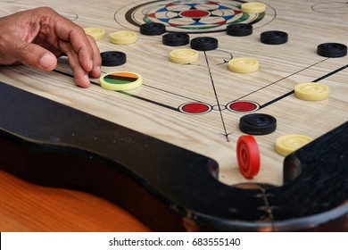 A game of carrom with pieces carrom man on the board carrom