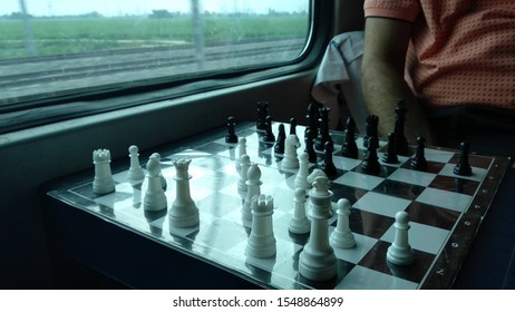 game of chess in train compartment in india with background of railway tracks and nature