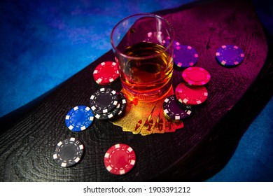 The game chips lie on the table next to a glass of alcohol on a black wooden surface. Game chips for betting in gambling. Poker chips. Playing cards.