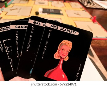 GAME OF CLUEDO; Dec 2016; a player studies their hand in this long running popular murder mystery board game