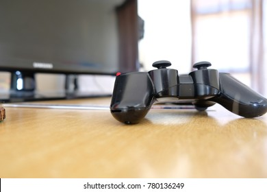 game console controller on a desk with screen behind it