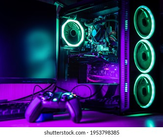 Game controller and pc rgb case on a wooden desk with green and purple lights