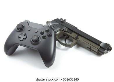Game controller and a real handgun near it - close up shot. Virtual and real life concept
